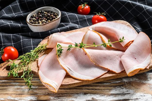Carni affumicate, lonza di maiale affumicata a fette. sfondo bianco. vista dall'alto Foto Premium