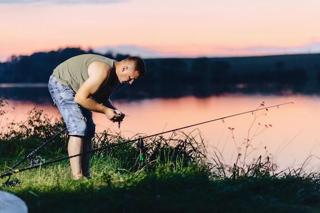 Carpa di cattura del pescatore nel lago nell'ora legale alla sera Foto Premium