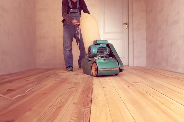 Carpenter lavora con una macchina elettrica per la macinazione del legno in una stanza Foto Premium