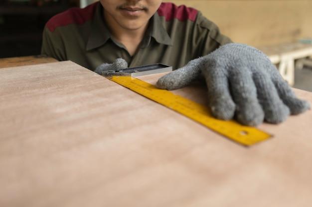 Carpentiere che lavora alle macchine per la lavorazione del legno in falegnameria. esperto falegname che taglia un pezzo di legno nel suo laboratorio di falegnameria. Foto Premium