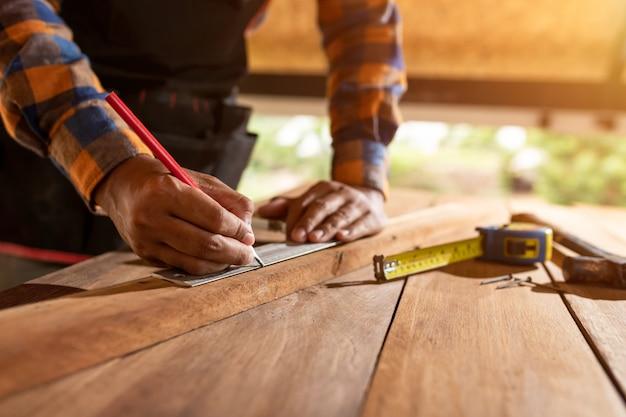 Carpentiere che lavora alle macchine per la lavorazione del legno in falegnameria. l'uomo lavora in un laboratorio di falegnameria usando il primo concetto di sicurezza indossando cuffie protettive. Foto Premium