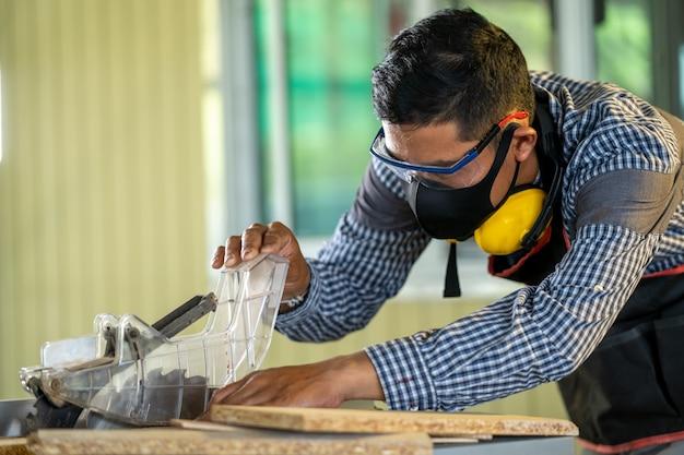 Carpentiere che lavora alle macchine per la lavorazione del legno in falegnameria, uomo che fa la falegnameria in carpenteria. Foto Premium