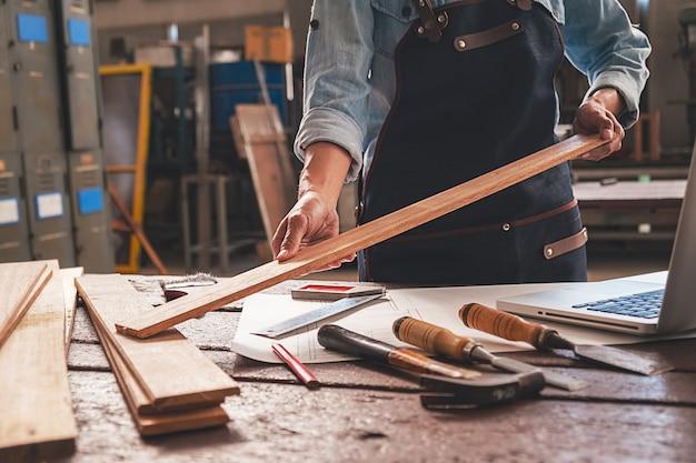 Carpentiere che lavora con l'attrezzatura sulla tavola di legno nel negozio di carpenteria. Foto Premium