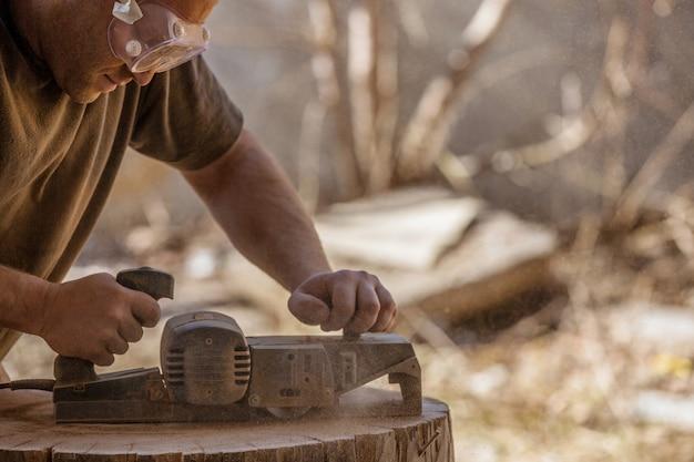 Carpentiere che lavora con pialla elettrica su ceppo di legno all'aria aperta, indossando occhiali. Foto Premium