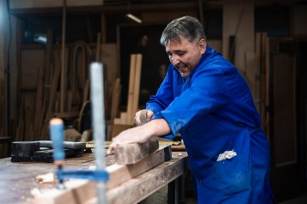 Carpentiere che lavora in officina, un lavoratore che spiana un albero con una pialla Foto Premium