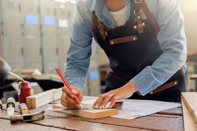 Carpentiere che lavora su macchine per la lavorazione del legno nel negozio di falegnameria Foto Premium