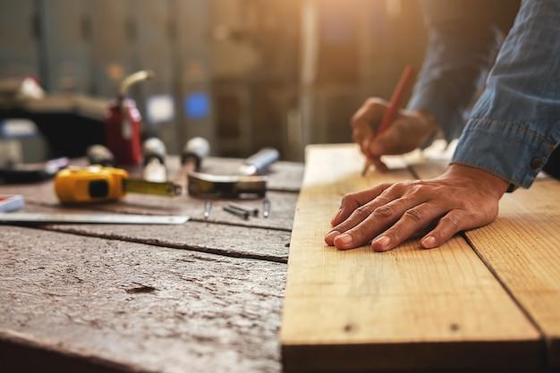 Carpentiere che lavora su macchine per la lavorazione del legno nel negozio di falegnameria. Foto Premium