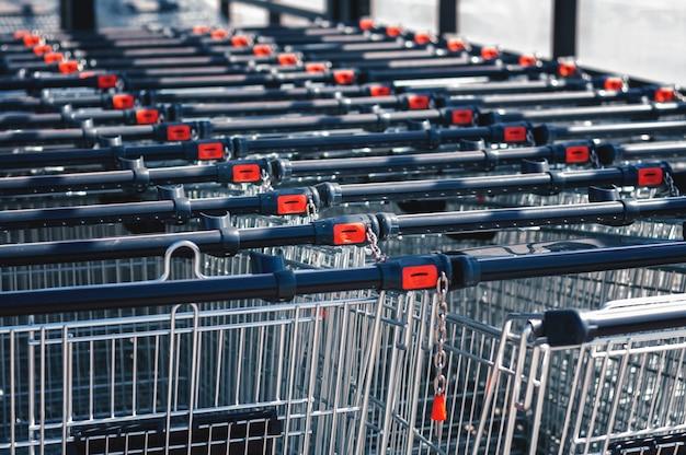 Carrelli della spesa nel negozio, assemblati in fila nel parcheggio. avvicinamento. Foto Premium