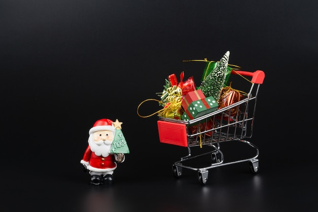 Carrello con albero di natale e scatole regalo in miniatura e babbo natale Foto Premium