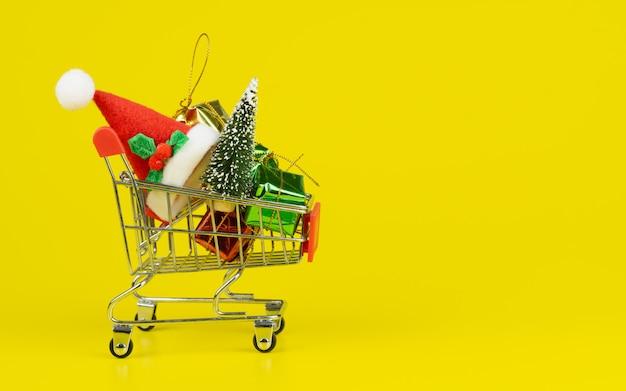 Carrello con l'albero di natale e contenitori di regalo miniatura su fondo giallo Foto Premium