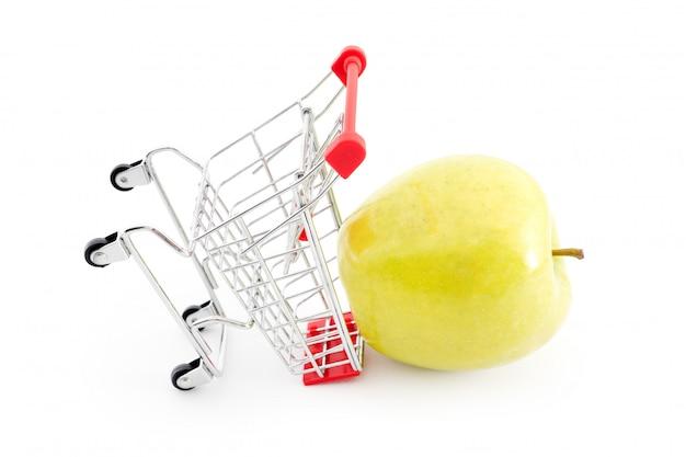 Carrello con la grande mela verde su bianco. l'acquisto di frutta dal supermercato. carrello completo del carrello della spesa del supermercato self-service. vendita, abbondanza, tema del raccolto Foto Premium