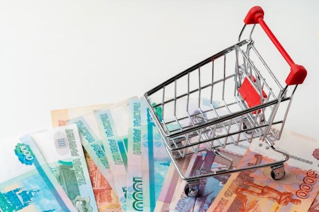 Carrello del giocattolo con soldi di rubli russi. salario vivente e concetto di potere d'acquisto Foto Premium