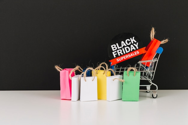Carrello del supermercato giocattolo con pacchetti e adesivo di vendita Foto Gratuite