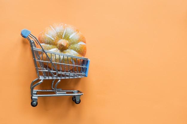 Carrello della drogheria con la zucca sull'arancia. shopping e vendita di halloween. vista piana, vista dall'alto. Foto Premium