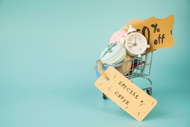 Carrello della spesa con sveglia, pezzetti di carta e maccheroni vicino tag di vendita Foto Gratuite