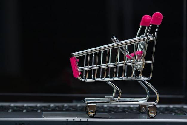 Carrello della spesa o carrello del supermercato con notebook portatile, e-commerce e concetto dello shopping online. Foto Premium