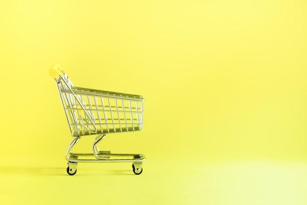 Carrello della spesa su sfondo giallo. carrello del negozio al supermercato. vendita, sconto, concetto di shopaholism. tendenza della società dei consumi Foto Premium