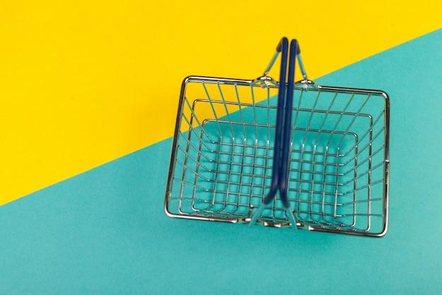 Carrello della spesa su un colorato Foto Premium