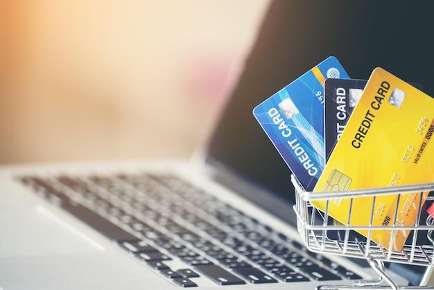 Carrello e carta di credito con il computer portatile sullo scrittorio Foto Premium