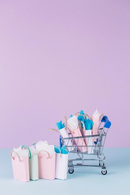 Carrello in miniatura pieno di sacchetti di carta Foto Gratuite