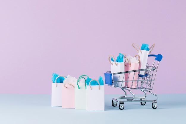 Carrello in miniatura riempito con sacchetti di acquisto di carta davanti a sfondo rosa Foto Gratuite