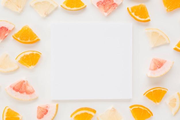 Carta bianca circondata con fette di agrumi colorati su sfondo bianco Foto Gratuite