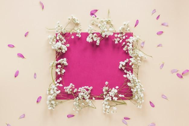 Carta bianca con rami di fiori sul tavolo luminoso Foto Gratuite