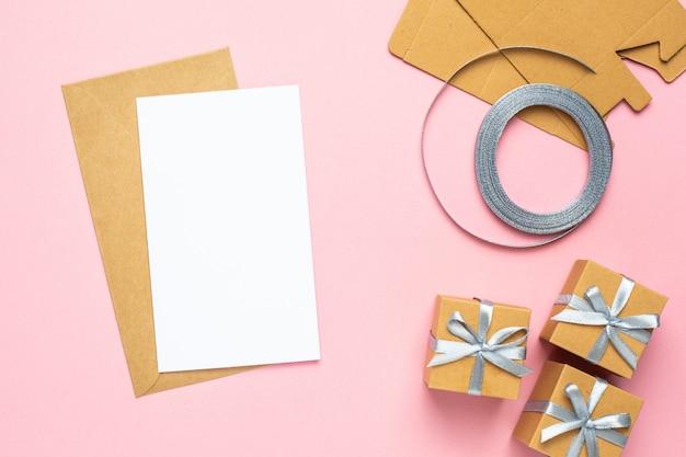 Carta bianca con regalo in composizione scatola per compleanno su sfondo rosa Foto Premium