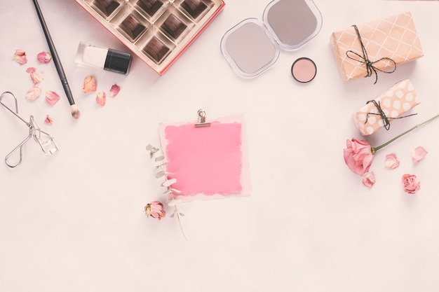 Carta bianca con scatole regalo, rose e cosmetici Foto Gratuite