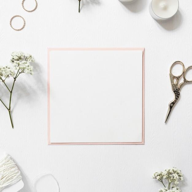 Carta bianca vuota circondata da anelli; gypsophila; stringa; candele e scissor su sfondo bianco Foto Gratuite