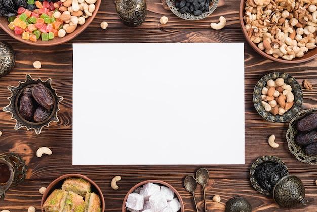 Carta bianca vuota circondata da frutta secca mista; date; lukum; baklava e noci sulla scrivania in legno per il ramadan Foto Gratuite