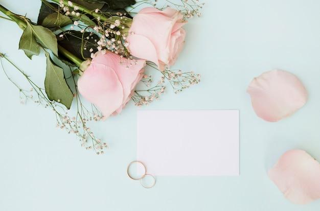 Carta bianca vuota con fedi nuziali e rose su sfondo blu pastello Foto Gratuite