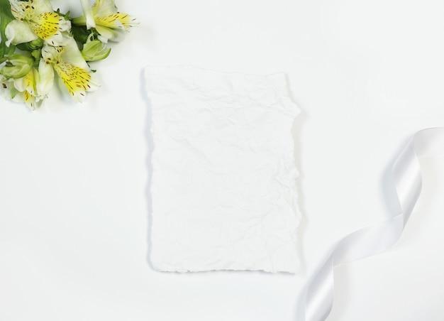Carta d'epoca con fiori e nastro su sfondo bianco Foto Premium