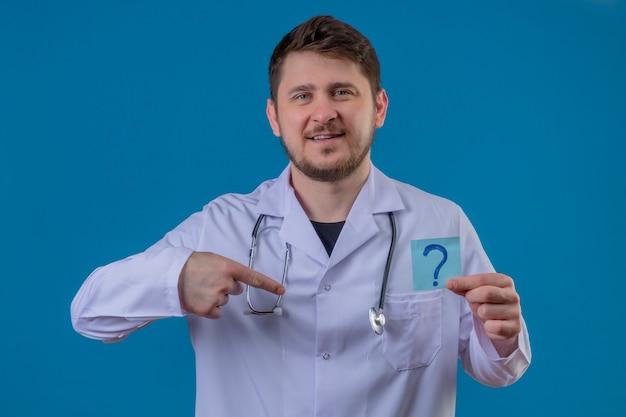Carta d'uso della tenuta delle camice e dello stetoscopio di medico del giovane con il punto interrogativo con il sorriso sul fronte che indica dito se stesso sopra fondo blu isolato Foto Gratuite