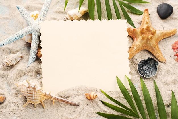 Carta dell'angolo alto sulla sabbia accanto ai crostacei Foto Gratuite