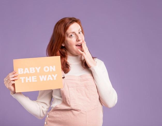 Carta della tenuta della donna incinta con il bambino sul messaggio di modo Foto Gratuite
