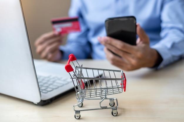 Carta di credito asiatica della tenuta dell'uomo d'affari facendo uso del computer portatile e dello smart phone Foto Premium