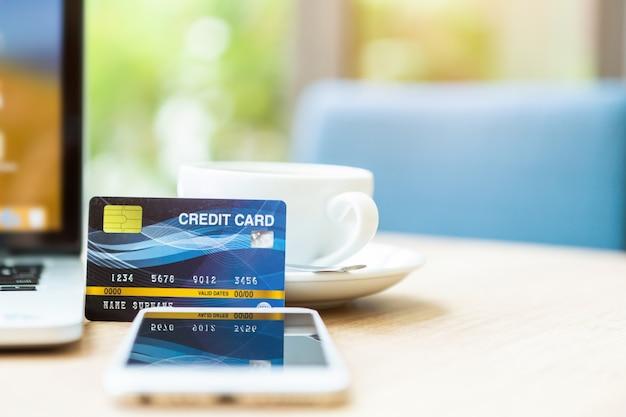 Carta di credito della tazza del computer portatile, dello smartphone e di caffè sulla tavola di legno Foto Premium