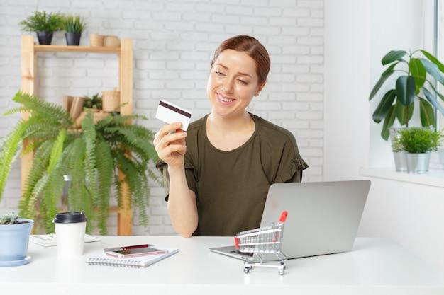 Carta di credito della tenuta della giovane donna e computer portatile usando. Foto Premium