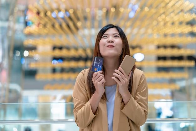 Carta di credito e telefono cellulare asiatici della tenuta della donna per acquisto online Foto Premium