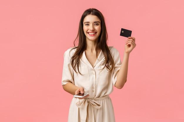 Carta di credito e telefono cellulare della tenuta della ragazza del brunette Foto Premium