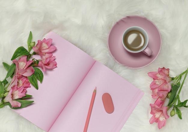 Carta di note rosa su fondo simile a pelliccia bianco con fiori e tazza di caffè Foto Premium
