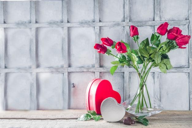 Carta di sfondo di san valentino con confezione regalo e bouquet di fiori di rosa Foto Premium