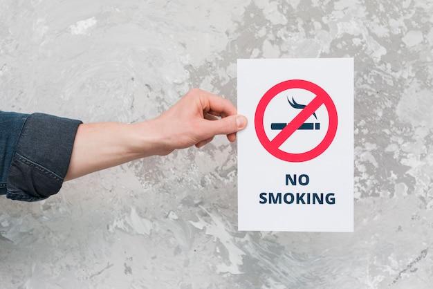 Carta maschio della tenuta della mano con il segno e testo non fumatori sopra la parete stagionata Foto Gratuite