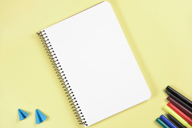 Carta piegata del mestiere e penna di pennarello vicino al blocco note a spirale in bianco su fondo giallo Foto Gratuite