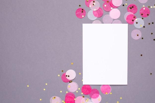 Carta regalo e coriandoli rosa con stelle dorate su grigio Foto Premium