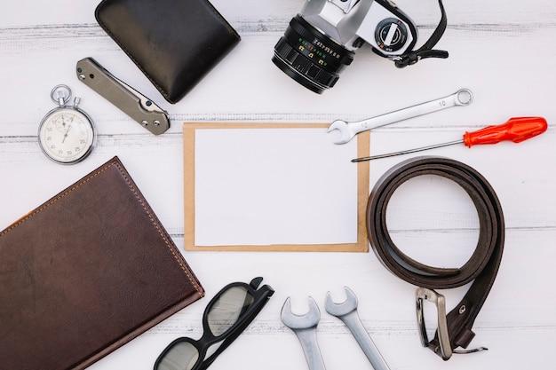 Carta vicino a fotocamera, notebook, cronometro, attrezzature di riparazione e cinturino in pelle Foto Gratuite