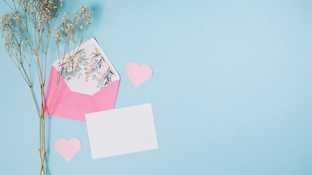 Carta vicino busta, cuori decorativi e pianta Foto Gratuite