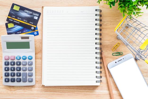 Carte di credito con il taccuino e il calcolatore su un desktop Foto Premium