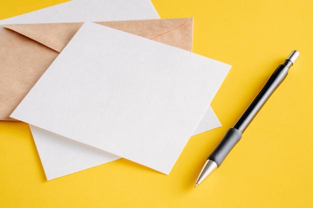 Carte di fogli vuoti di carta bianca, busta di kraft e penna su uno sfondo giallo. Foto Premium